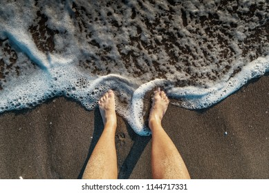 Male legs on the beach sand of the sea in summer on vacation.