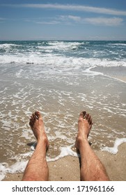 male legs on the beach in the water