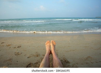 male legs on beach.Legs man lying on the beach shore of the Indian Ocean. Bay of Bengal Passikuda beach.