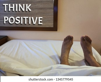 The male legs are resting on the bed with a white blanket. The wording 'Positive Thinking' is on the wall.