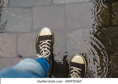 Male legs in sneakers and blue jeans walking through the rain puddle, top view