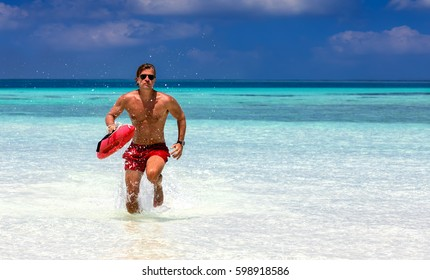 Male lifeguard running in turquoise waters