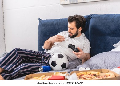 male loner playing video game in bedroom and removing spot on shirt