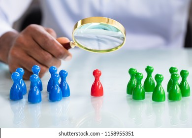 A Male Looking At Colorful Pawns With Magnifying Glass On The Reflective Desk
