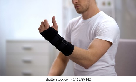 Male looking at hand with titan wrist support, orthopedic equipment, trauma