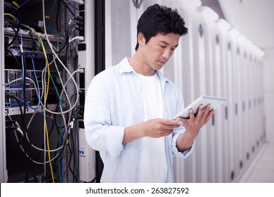 Male looking at his tablet computer against data center