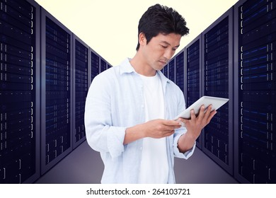 Male looking at his tablet computer against server hallway