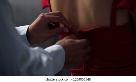 Male lover slowly unzips red dress from behind, unveiling bare female back