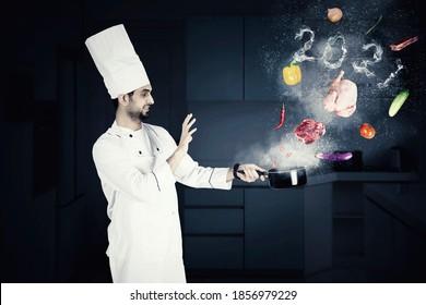 Männlicher Zauberkoch kocht auf einem Saucepan mit fliegenden Lebensmittelzutaten und Rauch in der Form der Nummern 2021 in der Küche