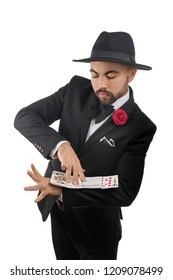 Male magician showing tricks with cards on white background