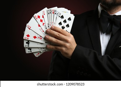Male magician showing tricks with cards on dark background, closeup