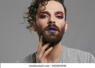 Male makeup look. Closeup portrait of a young bearded man,  wearing purple lipstick, winged eyeliner, pink eyeshadow. The guy looking at the camera, his lips slightly parted, his hand under his chin.