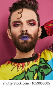 Male makeup look. Portrait of a young man in colorful shirt, wearing beard, quiff, purple lipstick, eyeliner, pink eyeshadow. The guy looking at the camera over pink background, one hand on his nape.
