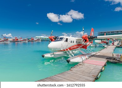 Male, Maldives – May 10, 2019: TMA - Trans Maldivian Airways Twin Otter seaplanes at Male airport (MLE) in the Maldives. Seaplane parking next to floating wooden jetty, Maldives