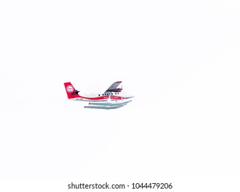MALE, MALDIVES - NOVEMBER, 27, 2016: Trans Maldivian Airways seaplane flies in the sky over Male. Isolated on white background. Copy space for text