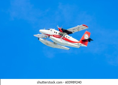 MALE, MALDIVES - November/27/2016: Seaplane of Trans Maldivian Airways airline is flying  in blue sky over Male. Isolated.