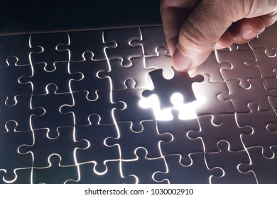 Male or Man Hand and Finger put Piece of Jigsaw in Place to Solve or Match Puzzle as Business Solution