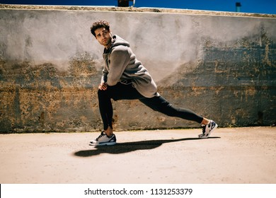 Male man in sporty tracksuit listening audio guidelines about workout during doing flexibility exercises outdoors, young strong hipster guy enjoying evening training actively on urban setting