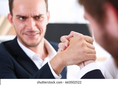 Male and man in suit hold hands in wrestle. Strong people battle portrait, female emancipation, feminism war, white collar rival game, aggressive expression, agreement effort, arbitration concept