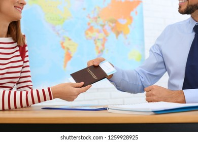 Male manager giving passport with ticket to client in travel agency, closeup