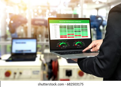 Male manager hand suit using laptop with machine real time monitoring sale rep performance scorecard system software. Blur robot arm machine in smart factory. Industry 4th iot , digital manufacturing.