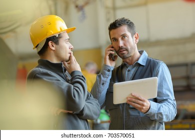 male manager in hard hat making a phone call