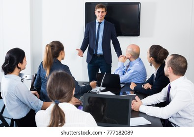 Male manager making presentation during business meeting in office