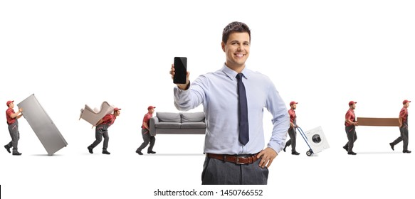 Male manager with a mobile phone and movers carrying furniture isolated on white background