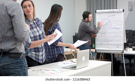 Male manager presenting pie chart on flipboard to his colleagues