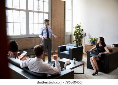 Male manager stands at an informal lounge meeting, close up