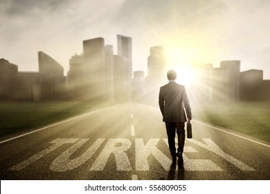Male manager walking on the street while carrying a briefcase with Turkey word at sunrise