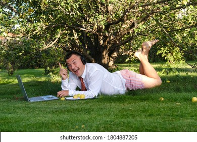 Male manager working in the garden, lying on the lawn, holding an online meeting. He laughs and rejoices. He is wearing a shirt with a tie, underpants. Stay home and quarantine