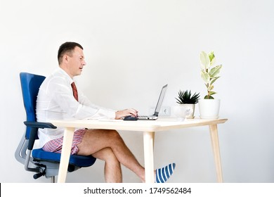 A male manager works at home remotely, holds an online meeting. He is wearing a shirt and tie and homemade shorts and slippers. Stay home and quarantine. Remote work, work on the Internet, remotely
