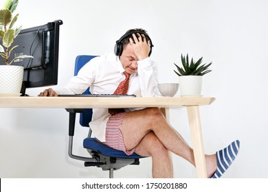 The male manager works remotely at home, holds online meetings. He is experiencing is tired and embarrassed. He is wearing a shirt and tie, underpants and slippers. Stay home and quarantine