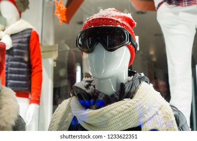 Male mannequin in store window during winter with ski gear, woolly hat, dark goggles, scarf, down jacket and fake snow on head. Shop window display.