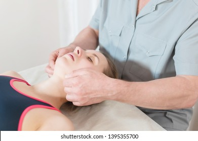 Male manual visceral therapist masseur treats a young female patient. Jaw muscles warm up