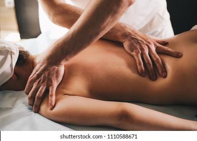 Male masseur doing girl massage in Spa salon close-up