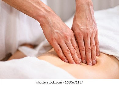 Male masseur makes visceral massage of internal organs through the stomach to a young woman in a spa room