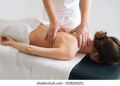 Male masseur massaging back and shoulder blades of young woman lying on massage table on white background. Concept of massage spa treatments.