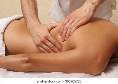 Male masseurs doing back massage, sexy blonde woman. Spa.