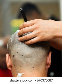 Male master shaves the head of the client
