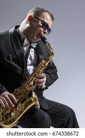 Male Mature Saxophone Player in Sunglasses Playing the Saxophone While Sitting on Chair in Studio Environment. Vertical Image
