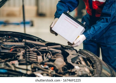 Male mechanic changing car battery, engineer is replacing car battery because car battery is depleted. concept car maintenance