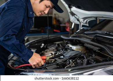 male mechanic charging battery of a car with electricity through jumper cables