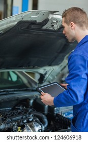 Male mechanic with digital tablet examining car engine