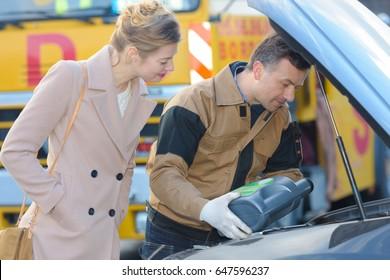 male mechanic filling oil tank of pretty woman customer
