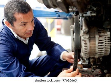 Male mechanic at the garage fixing a car