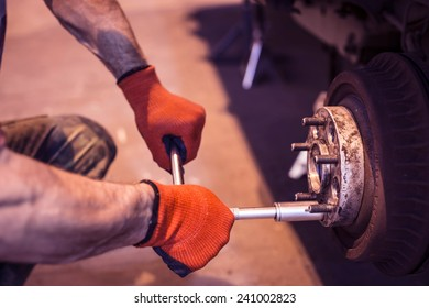 Male mechanic hands in gloves tightening the nuts using wrench. Mending, repair car in workshop.