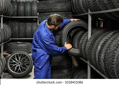 Male mechanic holding car tire in automobile store