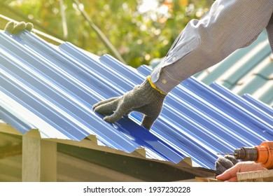 A male mechanic installs the roof of the house with all the equipment used for installation with skill